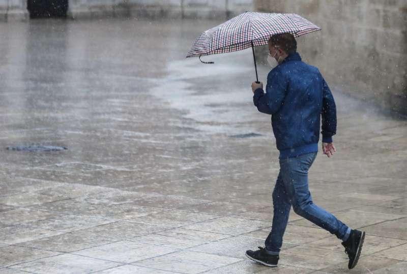 Una persona se protege de la lluvia con paraguas.