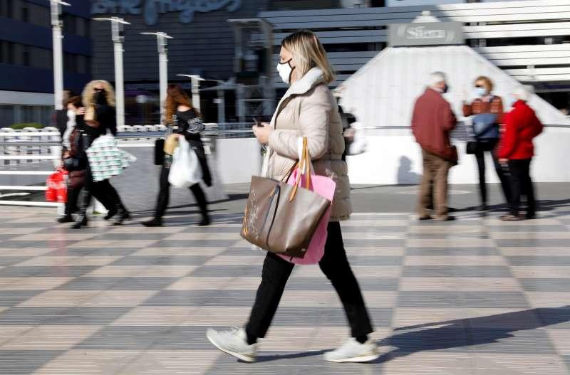 Varias personas cargadas con bolsas de la compra pasean ante un centro comercial.