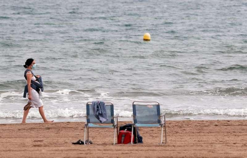 Una mujer pasea por la playa de la Malvarrosa de València. EFE/Kai Försterling/Archivo