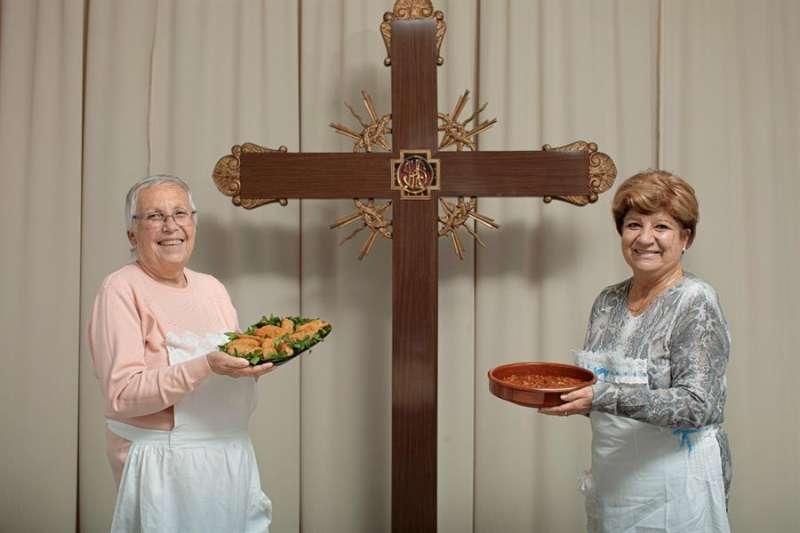 Amparo Pons (i) y Vicenta Mengual (d) posan con los platos preparados por ellas. EFE