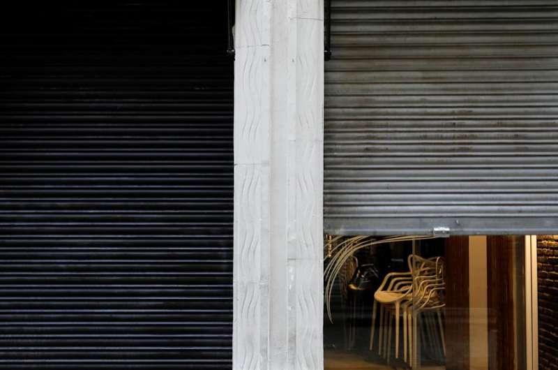 Sillas recogidas en un restaurante de València que cierra la persiana, en cumplimiento de las medidas anticovid. EFE/Ana Escobar.