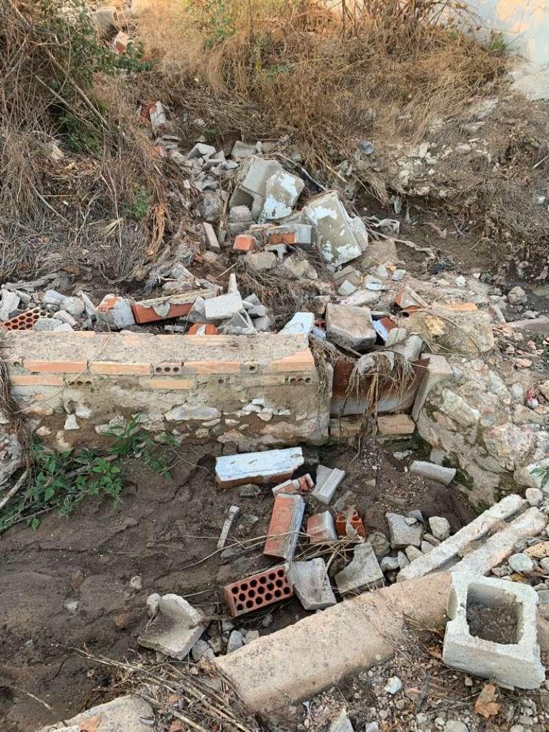 Restos del escombros en la acequia.