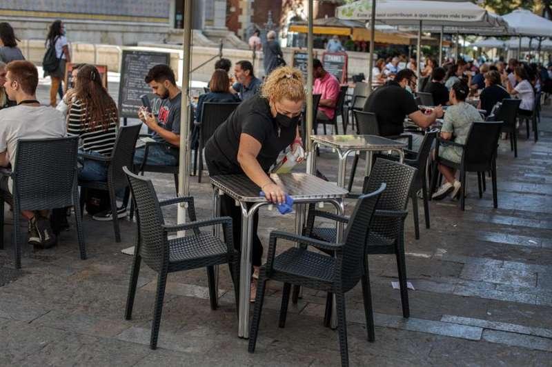 Una camarera desinfecta una mesa de una terraza en el centro de València. EFE