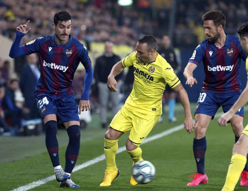 Santi Cazorla (c) disputa el balón con los jugadores del Levante, José Gómez Campaña (i) y Jorge Miramón. EFE