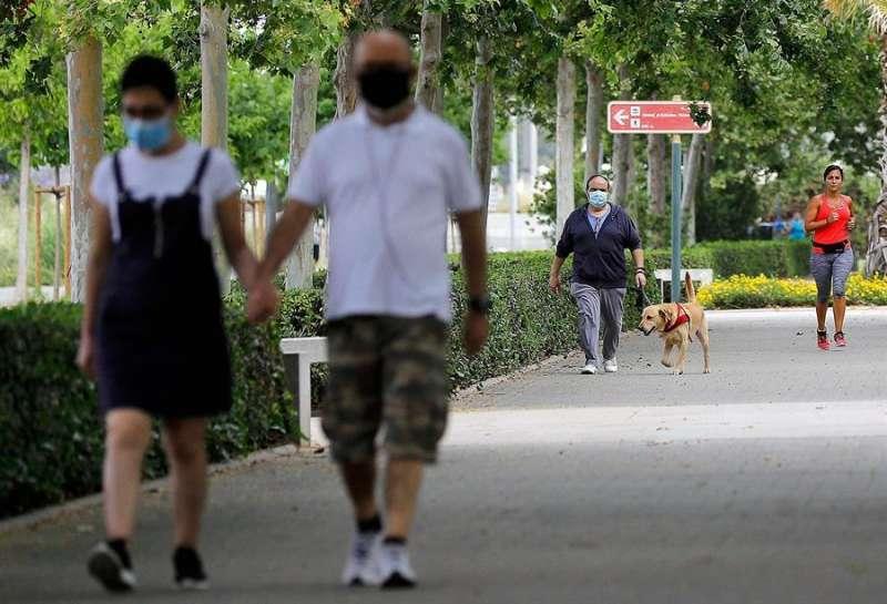 Varias personas pasean con mascarilla en estos días. EFE