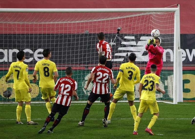 El portero del Villarreal Sergio Asenjo (d) despeja un balón cabeceado por Íñigo Martínez (c, arriba), del Athletic, durante el partido de Liga en Primera División que disputaron en el estadio de San Mamés, en Bilbao. EFE/Luis Tejido