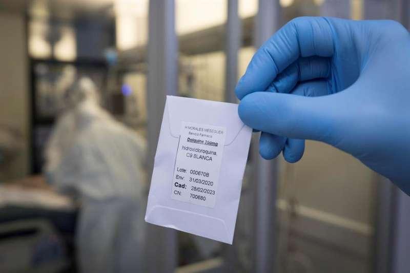 Una enfermera de una unidad de cuidados intensivos (UCI), muestra una dosis de hidroxicloroquina