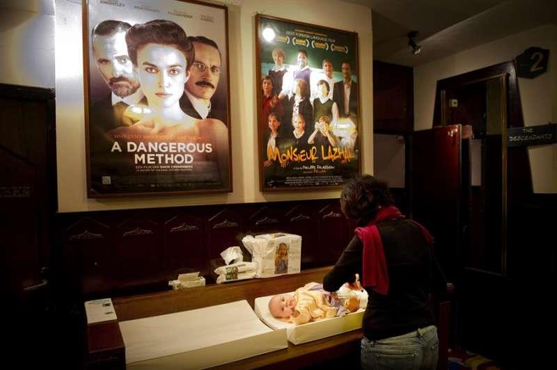 Una mujer cambia el pañal de su bebé en el baño de la sala de cine. EFE/Archivo
