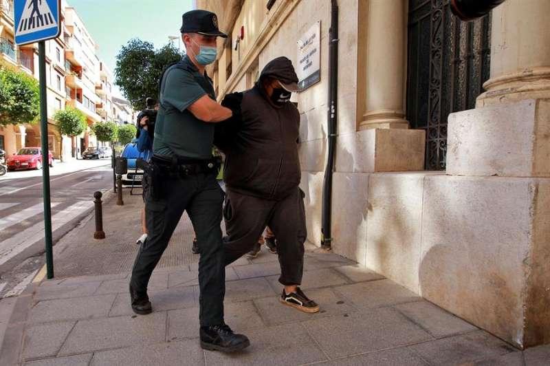 Un agente de la Guardia Civil traslada este sábado al Juzgado a uno de los detenidos por su supuesta participación en la violación. EFE