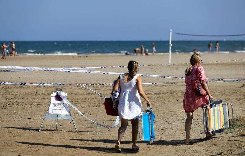 Dos bañistas pasan junto a una señal que informa de la prohibición de bañarse. EFE/Archivo