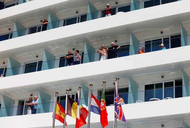 Varios turistas asomados a los balcones de su hotel en la playa de Benidorm (Alicante). EFE