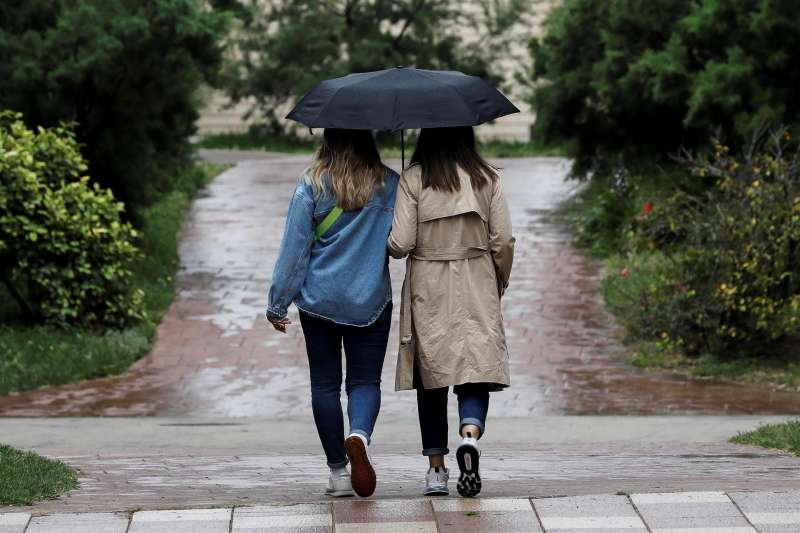 Dos personas se protegen de la lluvia con un paraguas en una imagen de archivo.