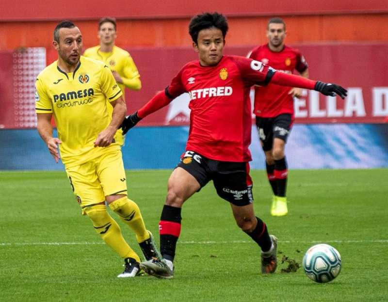 El delantero japonés del RCD Mallorca Takefusa Kubo disputa el balón con el centrocampista del Villarreal Santiago Cazorla, durante el partido de lap rimera vuelta. EFE