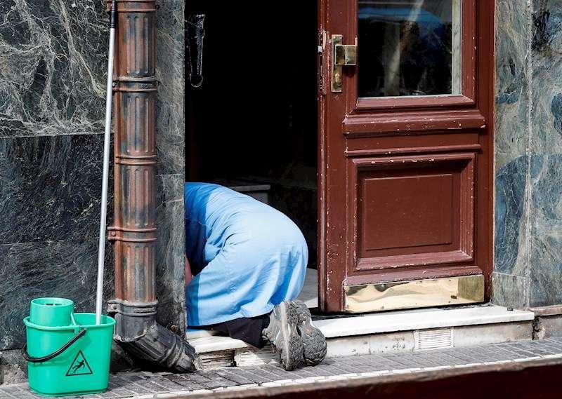 Una mujer limpia un portal. EFE/Archivo