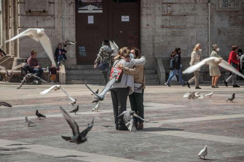 Dos personas se abrazan en una céntrica plaza de València, un gesto difícil de ver durante la pandemia.