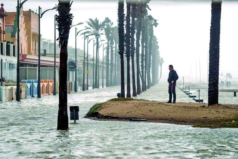 El agua inunda el paseo de La Patacona de Alboraya. EFE