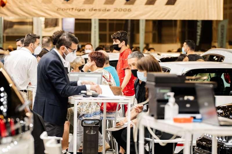 Varias personas reciben información en uno de los expositores de la Feria del Vehículo de Ocasión, en una imagen facilitada por los organizadores. EFE