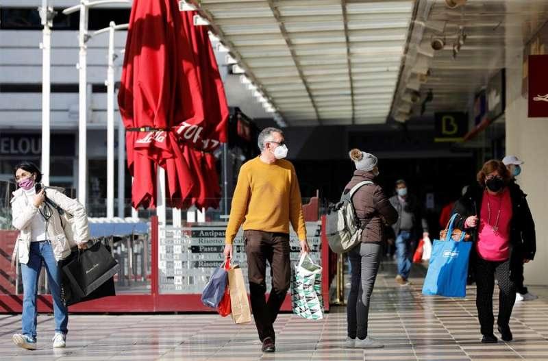 Varias personas cargadas con bolsas de la compra pasean por el exterior de un centro comercial. EFE