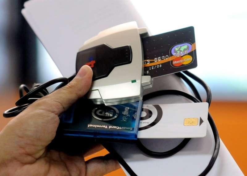 Un agente muestra un dispositivo para duplicar tarjetas de crédito incautado una operación policial.
