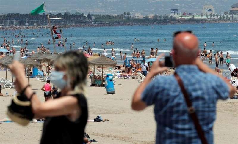 Dos turistas con mascarilla frente a una playa valenciana