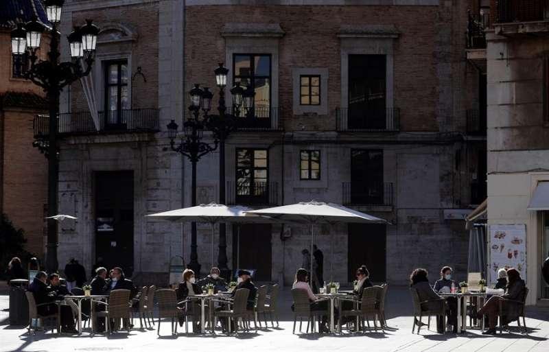 Un grupo de personas aprovecha una terraza al sol durante este miércoles se mantiene el frío polar. EFE/Manuel Bruque