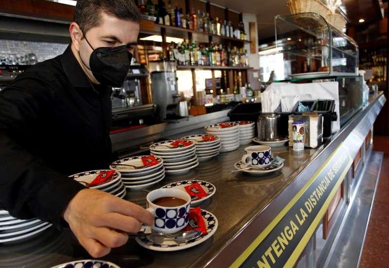 Un camarero pone un café en un bar.